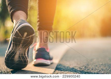 Women Runner Feet On Road In Workout Wellness Concept.