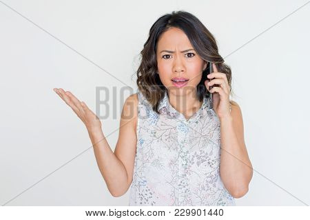Closeup Of Angry Asian Woman Speaking On Mobile Phone And Shrugging Shoulders. Concerned Young Lady