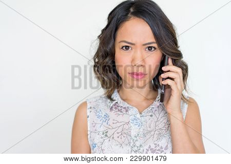 Closeup Of Frowning Asian Woman Talking On Smartphone And Getting Bad News. Serious Young Lady Makin