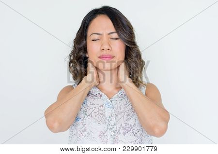 Upset Asian Woman With Closed Eyes Touching Neck. Frustrated Young Lady Suffering From Neck Ache. St