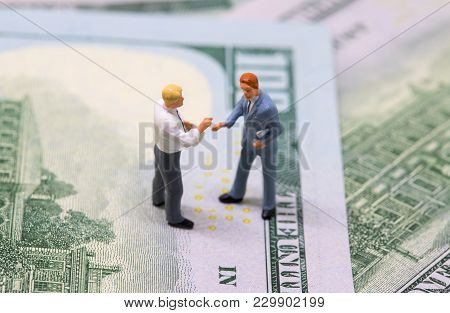 Businessmen Figurines Shaking Hands On Cash. Tiny Businessmen Models On Money Background. Finance Or
