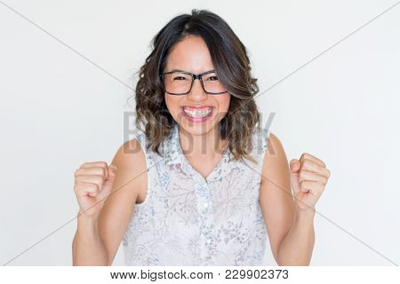 Amazed Asian Girl Clenching Fists In Success And Broadly Smiling. Smart Student Making Winning Gestu