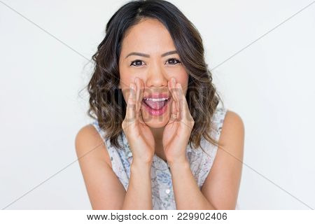 Smiling Asian Woman Shouting Loud With Hands At Mouth. Young Lady Announcing News Or Respiring Gossi