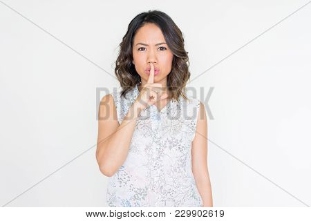 Serious Young Asian Woman Covering Mouth With Index Finger. Conspiratorial Young Lady Asking To Keep