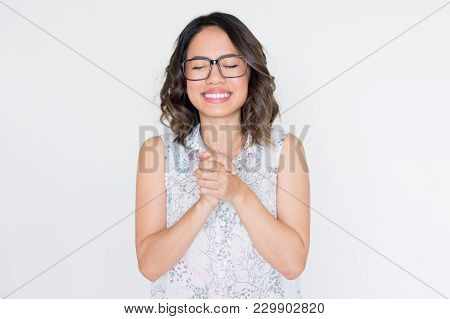 Smiling Asian Girl In Glasses With Closed Eyes Clasping Hands. Student Happy About Successful Exams