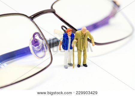 Miniature Old Couple And Optical Glasses. Senior Age Couple Walking With Support. Aged People Health