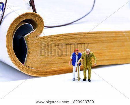 Senior Couple Miniature Figurine With Book And Glasses On Background. Elderly Couple In Library Conc