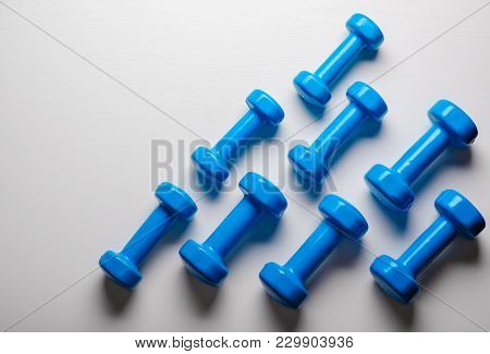 Many Blue Dumbbells On A White Background ,concept Preparing To Fitness Sports Equipment Top View Mo