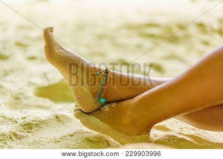 Woman feet leg near beach sand red nails