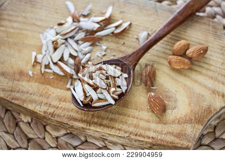 A Bunch Of Whole And Chopped Almond Nuts On A Wooden Board And In A Wooden Oak Spoon On A Rattan Tab