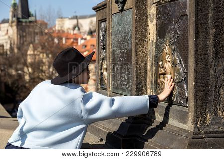 Prague, Czech Republic - March 16, 2017: Woman Touching The Statue Of Nepomuk On Charles Bridge, Whi