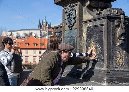 Prague, Czech Republic - March 16, 2017: People Touching The Statue Of Nepomuk On Charles Bridge, Wh