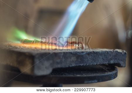 Craft Jewelery Making With Flame Torch. Jeweler Processing Metal Bar By Heating It Up. Annealing Is