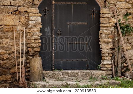 Old Medieval Doors With Broom And Woods In Brick Wall Fortress. Image Made In Old Color Style