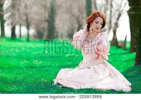 Portrait Of A Young Redheadd Girl In Victorian Style Dress Sitting On Grass In Springtime