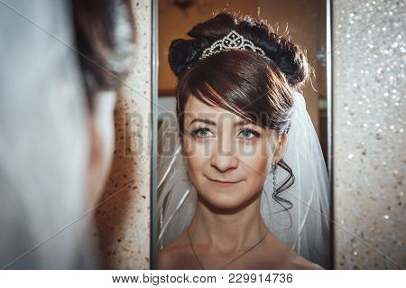 Portrait Of Slender Bride In A White Veil Indoors