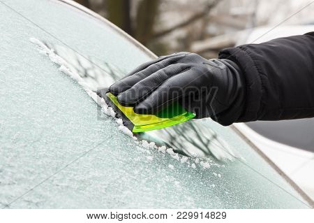 Hand Of Man In Glove Scraping Ice And Snow From Car Windscreen
