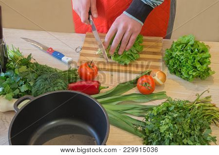 Man Cooking Healthy Meal In The Kitchen. Cooking Healthy Food At Home. Male In Kitchen Preparing Veg