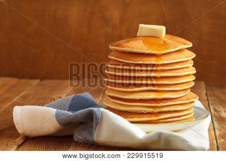 Stack Of Pancakes With Honey And Piece Of Butter On Plate Which Stands On Napkin On Wooden Table. Co