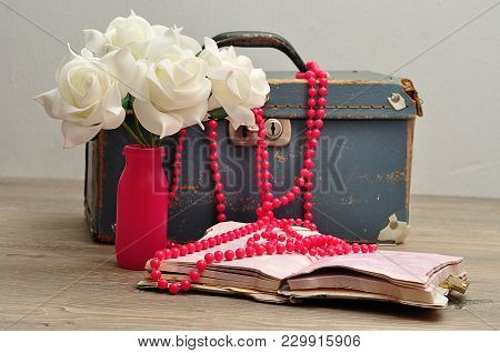 An Old Worn Out Blue Suitcase With A Bunch Of Artificial White Roses, A String Pink Beads And A Note