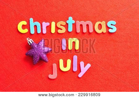 The Words Christmas In July In Colorful Letters On A Red Background And A Purple Star Shape Christma