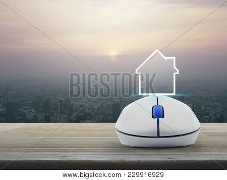 House Icon With Copy Space With Wireless Computer Mouse On Wooden Over Modern City Tower At Sunset,