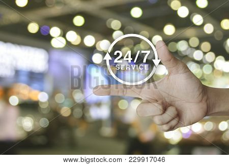 24 Hours Service Icon On Finger Over Blur Light And Shadow Of Shopping Mall, Full Time Service Conce