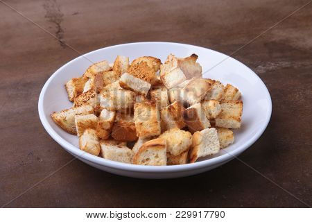Delicious Crispy Croutons, Crumbs Of Bread In White Plate. Ready For Cooking