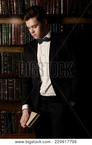 Portrait of a stylish handsome young man in luxurious vintage apartments. Fashion shot. Men's clothing and accessories.