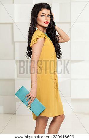 Smiling Brunette Woman In Trendy Yellow Dress And Blue Handbag. Fashion Portrait Of Beautiful Brunet