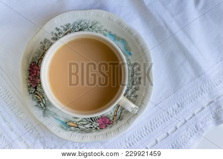 Cup Of Tea Close Up On Lace Cloth In Vintage Cup And Saucer - Top View Background
