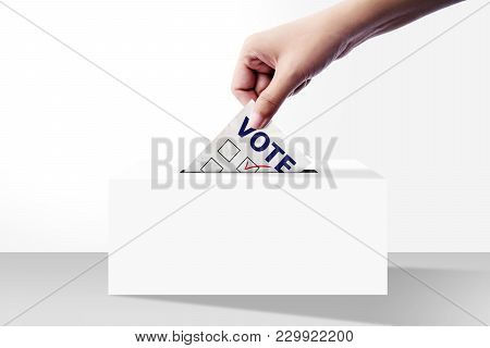 Close Up Of Hand Holding Voting Paper For Election Vote Into The Ballot Box On White Background