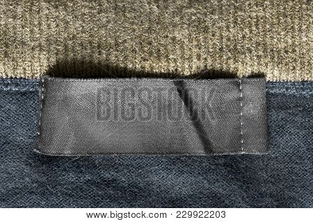Blank Black Textile Clothes Label On Knitted Background Closeup