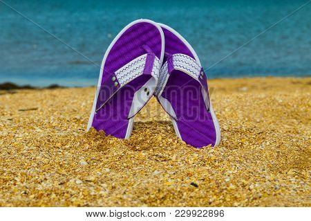 Pair Of Flip Flops Sticking Up On A Sandy Sea Beach