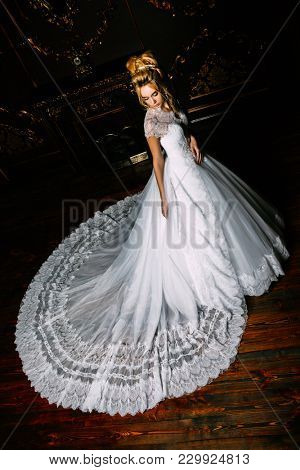 Full length portrait of a beautiful bride woman in luxurious white wedding dress. Luxurious vintage apartments. Wedding fashion.