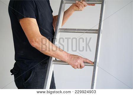 An Electrician Holds An Aluminum Ladder. The Builder Carries An Aluminum Stepladder. Worker Of The P