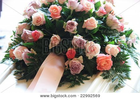 Pink Sympathy Flowers On A White Coffin