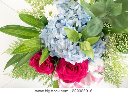 Roses And Blue Fragile Flower And Leaves In The Beautiful Flower Bouquet