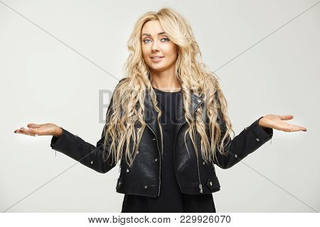 Puzzled Female Horizontal Portrait Of A Blonde With Long Hair Lifting Shoulders As A Sign Of Ignoran