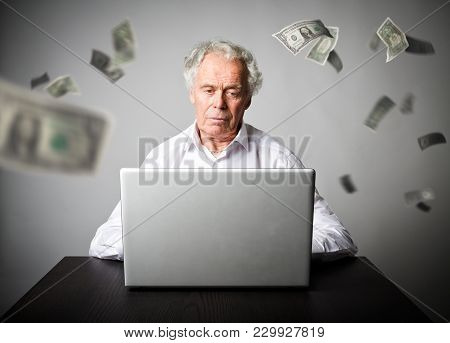 Old Man Is Using A Laptop To Browse The Net. Old Man In White Earns Money On The Internet. Working A