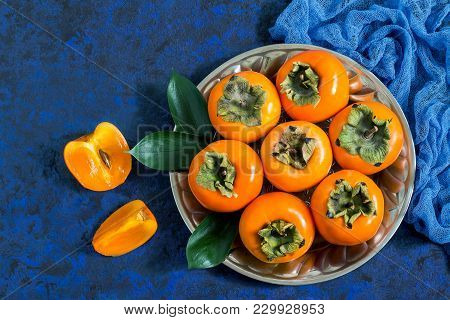 Ripe Persimmon On Metal Plate With Blue Gauze Napkin On Blue Textured Background. Persimmon Is Sourc