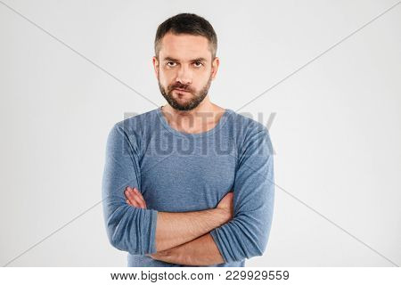 Image of angry displeased man standing isolated over white background wall. Looking camera.