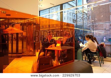 Sweden, Stockholm - February 10, 2018: People sitting behind orange wall in Max hamburger restaurant in city center of Stockholm