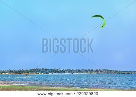 Kalpitiya, Sri Lanka - January 2, 2018. Kite Filled With Wind Pulls A Young Male On A Kiteboard Thro