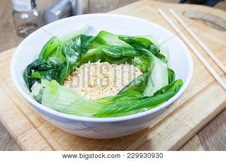 Uncooked Instant Noodles And Pak Choy Or Chinese Cabbage In White Bowl