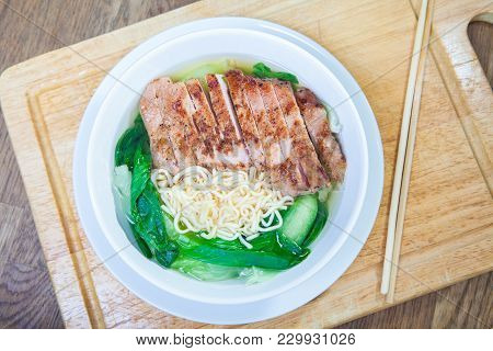 Instant Noodles With Fried Pork Cutlet With Pak Choy Or Chinese Cabbage In White Bowl And Plate On W