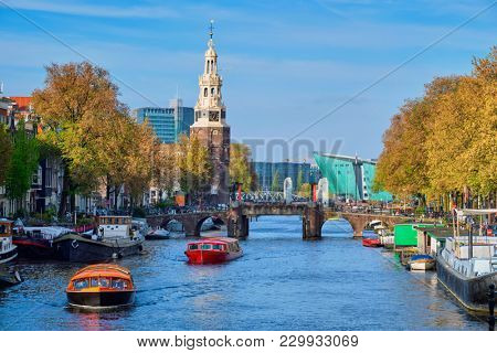 Amsterdam cityscape with canal boats and medieval houses and NEMO Science museum and Montelbaanstoren Tower. Amsterdam,  Netherlands