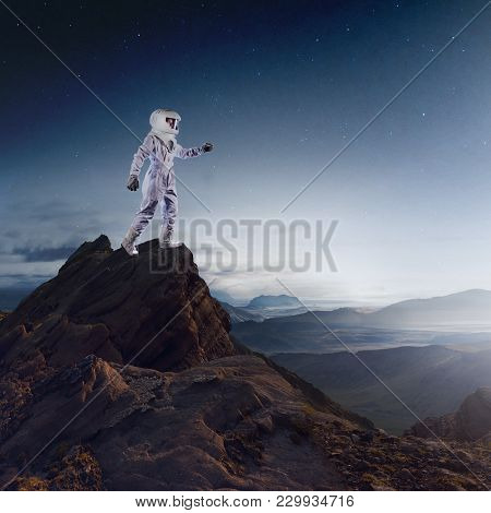 Futuristic Astronaut On The Planet, Standing On Top Of A Mountain And Stretches His Hand Away