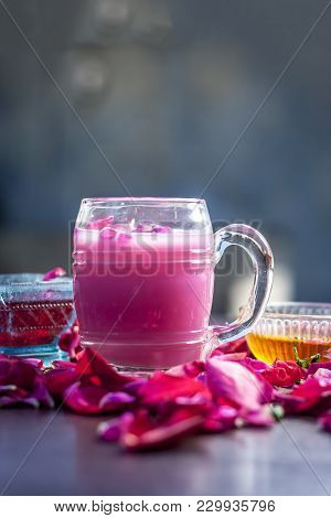 Indian/Asian popular summer drink i.e. Gulab Shake or Rose shake consisting of milk,rose syrup,sugar and honey with sabja seeds or sweet basil seeds in a transparent glass,with all ingredients. poster