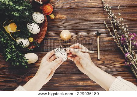 Hands Painting Easter Eggs With Beeswax Top View. Easter Holiday Concept. Eggs, Buds, Flowers, Candl
